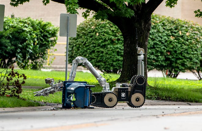 A robot from the Illinois Secretary of State inspects a garbage can after a reported explosion near the intersection of  West Lawrence Avenue and Witherspoon Drive in Springfield, Ill., Monday, July 12, 2021. [Justin L. Fowler/The State Journal-Register]