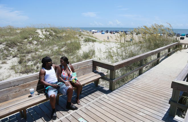 A couple sits on a bench at a beach crossover near the Tybee Island Pier.