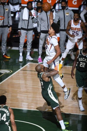 Former UNC and current Phoenix Suns forward Cameron Johnson dunks on Milwaukee Bucks forward P.J. Tucker during the third quarter of Game Three of the 2021 NBA Finals on Sunday, July 11, 2021. The Suns lost Game Three but lead 2-1 in the best-of-seven series.