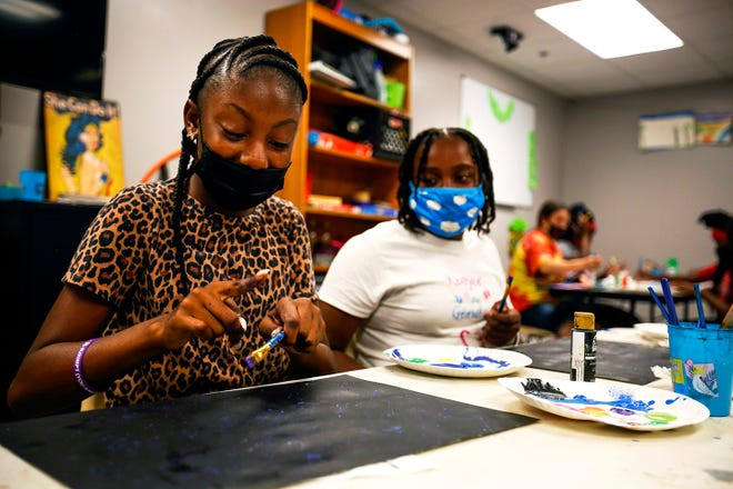 Two children splatter paint onto papers to create galaxy pictures ahead of snack time at the Girls Place summer program on Friday, July 9, 2021 in Gainesville, Fla. [Chasity Maynard/Special to The Sun]