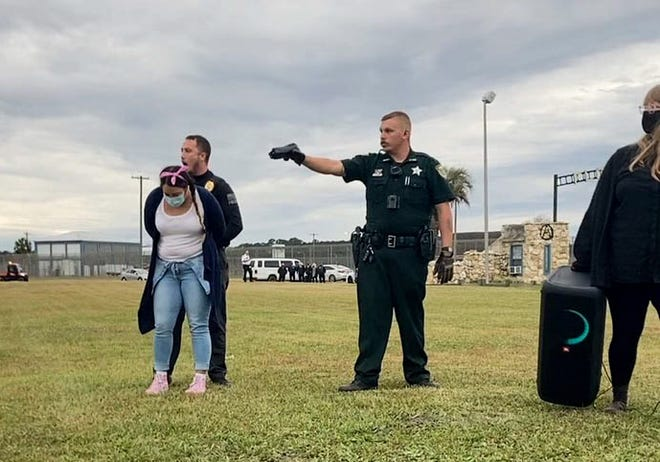 A law enforcement officer points a Taser toward a protestor arrested Dec. 6 outside Florida State Prison in Raiford.