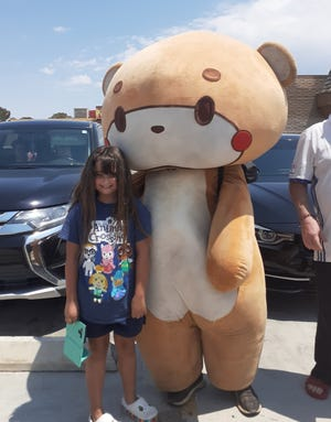 Kayla Strollo poses with Bearsun during his travels in the Victor Valley.