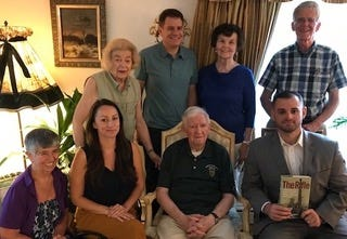 """Friends and colleagues gathered at the home of Pat Flynn as author Andrew Biggio presented him with a copy of his book, """"The Rifle."""" Pictured, from left, first row: Lorain Marquis, Lexington Veterans Association; Gina Rada, Veterans' Services director, Lexington/Bedford/Carlisle; Pat Flynn; and Andrew Biggio. Second row: Edith Flynn; Doug Lucente, vice chair, Select Board; and Linda Dixon and Jim Ramsey, Lexington Veterans Association."""