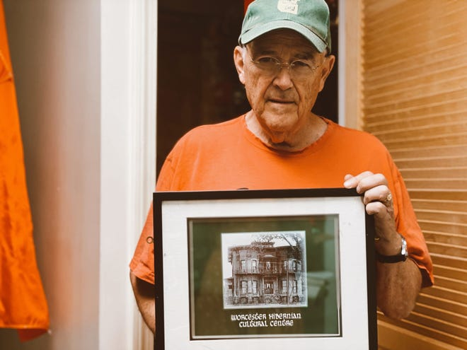 Founding President of the Worcester County Hibernian Cultural Foundation Paul Foley holds a photo of the John T. Cahill House taken in 1894.