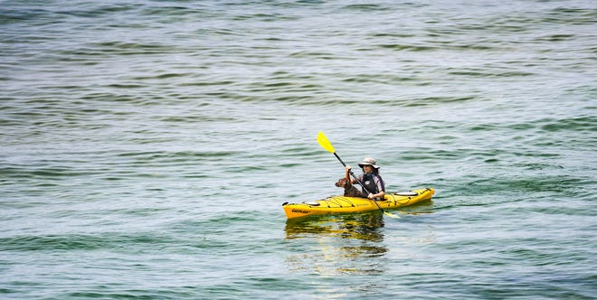 "Jennafer VandeVegte of Kentwood kayaks with five-year old labradoodle ""Buddy"" Sunday morning, July 4, 2021."