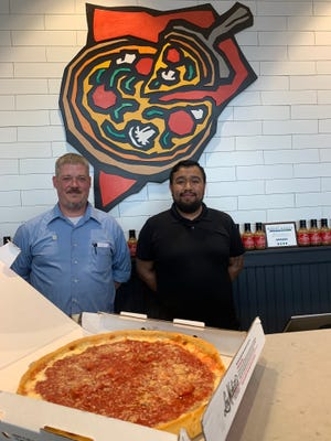Manager Brandon Nicholas and general manager Daniel Velazquez stand between the firm's logo and a freshly made deep-dish pizza at Lou Malnati's Pizzeria in Waukesha on its first day in business locally. The new location is a takeout/delivery only store at 2720 N. Grandview Boulevard, which previously was home to a Firehouse Subs restaurant.