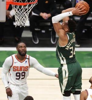 Bucks forward Giannis Antetokounmpo dunks the ball as Phoenix Suns forward Jae Crowder watches during Game 3. Antetokounmpo scored 41 points.