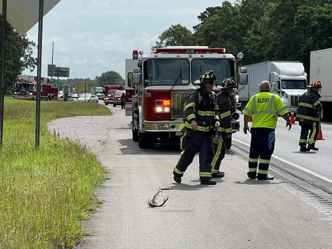 Firefighters and ALDOT road crews worked to contain a spill and clean up a wreck after a truck overturned at the Interstate 85 and Taylor Road exit.