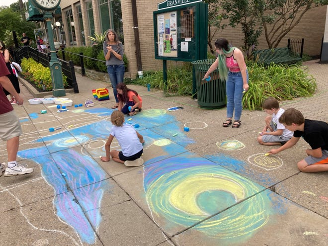 """Sarah Gray (pointing) assists local youths in recreating Van Gogh's """"The Starry Night"""" in chalk on the sidewalk near Village Hall on July 10."""