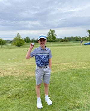 Thomas Fliss, a 9-year-old from Canton, shows off his hole-in-one ball he recorded at the Fox Hills Golf Course camp.