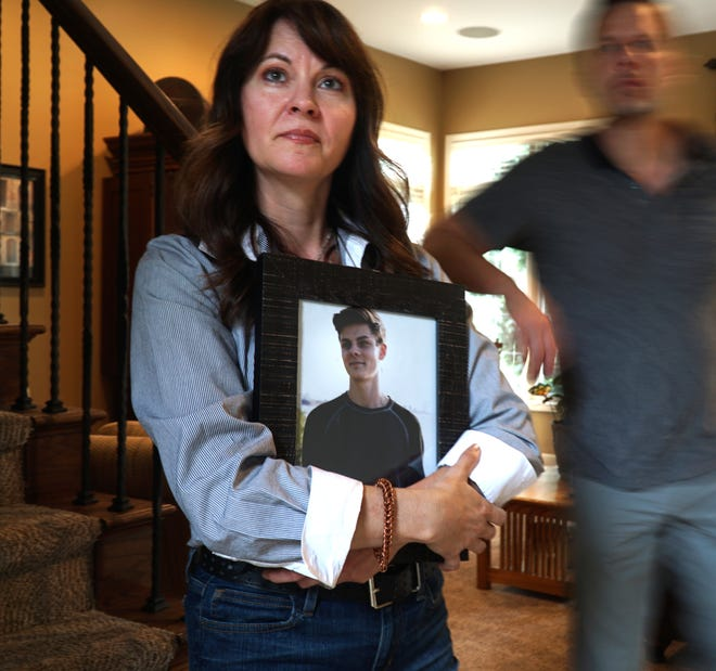 Gabriella Duhn holds a portrait of her late son Dominic in her Northville home on July 12, 2021. The Duhn family is concerned that the motorist who hit and killed Dominic in 2020, Gustavo Godinez, is still driving even after receiving a speeding citation well after hitting Dominic along Sheldon Road. Drew Duhn, Dominic's father, is at right.