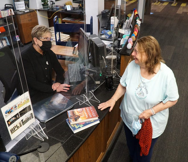 Janet Francis prepares to check out some books from Birmingham's Baldwin Public Library on July 12, 2021 as clerk Elizabeth Volpe, left, assists. The library has decided to no longer collect overdue fines from its patrons.