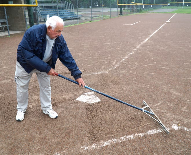 Gerald Greener rakes the batters' box of Plymouth's Don Massey Field in the rain on July 12, 2021.