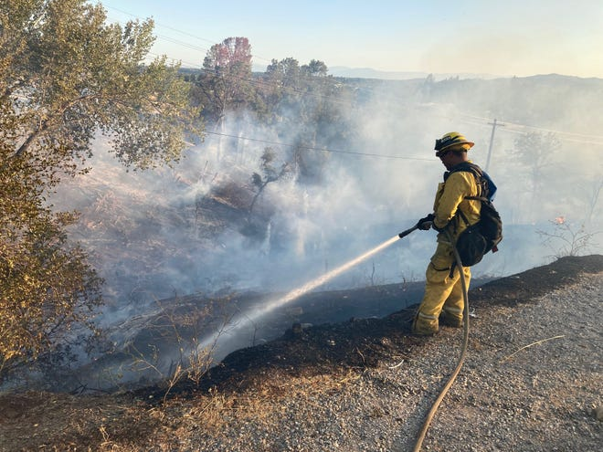 A Redding firefighter hoses down a hotspot on a fire that burned 5 to 7 acres west of North Market Street and south of Lake Boulevard on Sunday night, July 11, 2021.