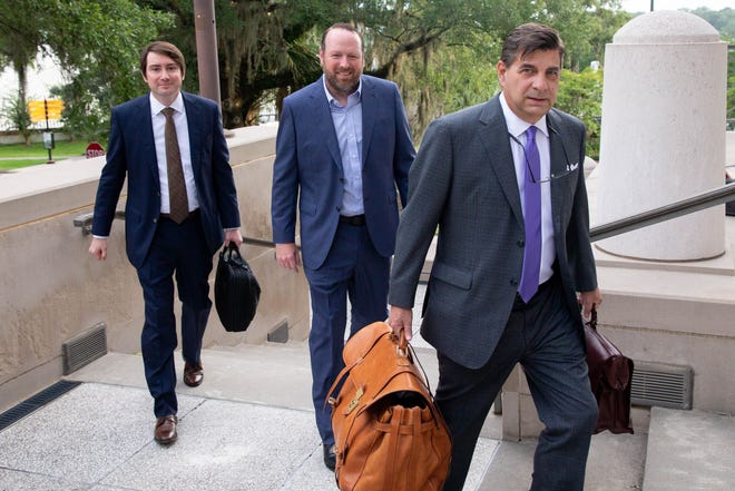 """John """"J.T."""" Burnette and his attorney Tim Jansen, right, walk into the U.S. Courthouse in downtown Tallahassee on the first day of Burnette's trial for racketeering, extortion, fraud and making false statements Monday, July 12, 2021."""