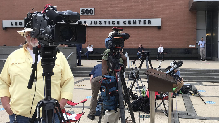 Members of the media wait outside the Leonard L. Williams Justice Center on Monday for Elon Musk to arrive at the courthouse.  Capitol Police allowed the billionaire to enter the building through another entry point other than the main entrance.