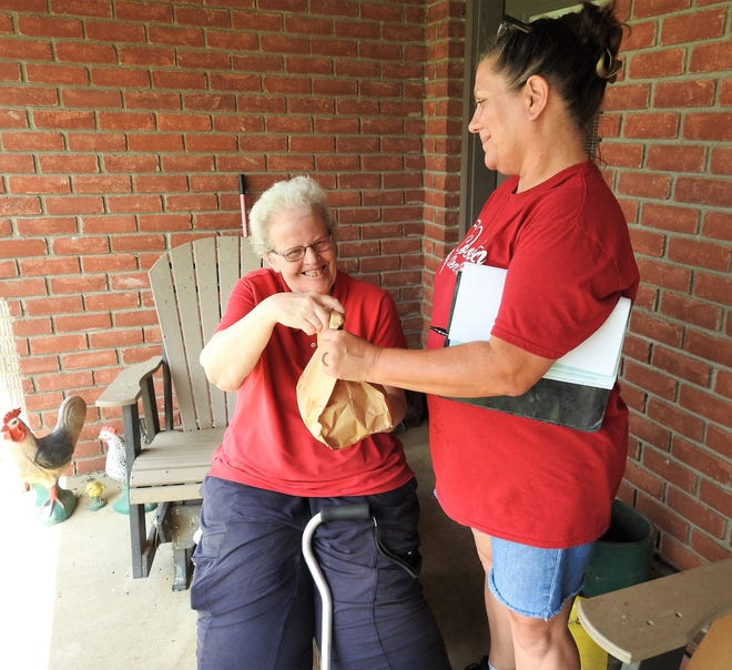 Maurita Garber receives a home-delivered meal from driver Dana Kittner through from the Coshocton Senior Center. The center has yet to reopen from the pandemic, but continues offering vital programs to elderly in the community.