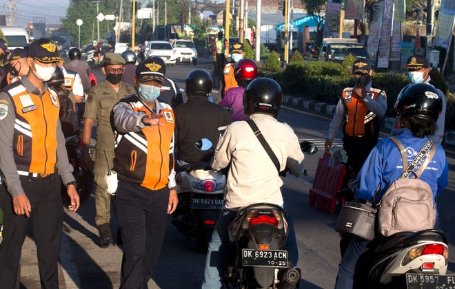Security officers check motorcyclists at a check point during the imposition of an emergency restriction to curb the spread of coronavirus outbreak in Denpasar, Bali, Indonesia on July 10, 2021.
