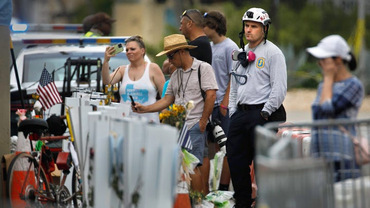 A member of the New Jersey Search and Rescue Task Force 1 joins others at the memorial for victims of the Champlain Towers South condo in Surfside, Fla. Monday, July 12, 2021.