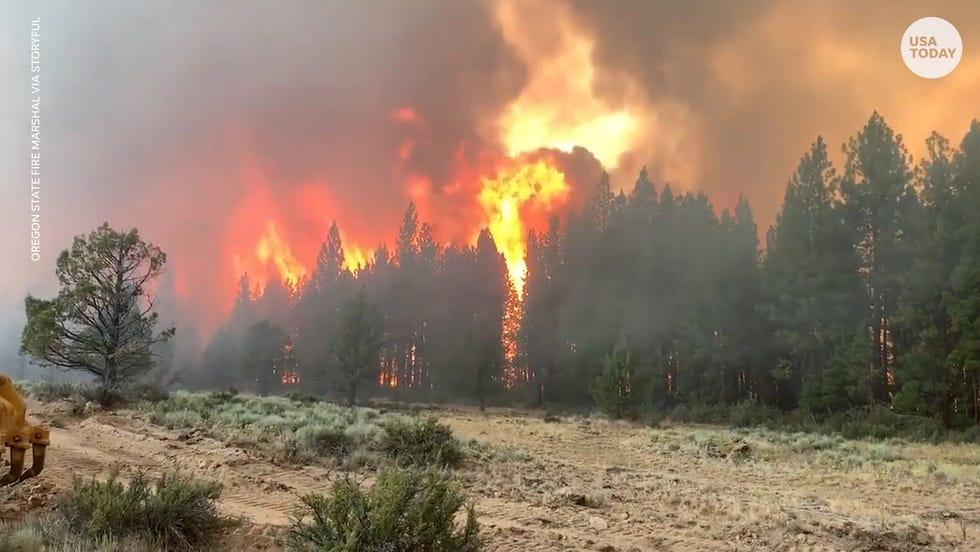 Nearly 70 active wildfires have destroyed homes and burned through about 1,562 square miles (4,047 square kilometers) — a combined area larger than Rhode Island — in a dozen mostly Western states, according to the National Interagency Fire Center.