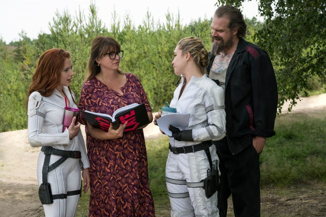 """Director Cate Shortland (second from left) goes over a scene with  stars Scarlett Johansson, Florence Pugh and David Harbour on the set of """"Black Widow."""""""