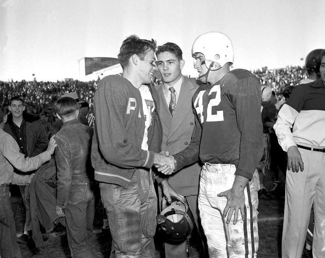In this Jan. 1, 1954 file photo, Rice fullback Dicky Maegle, left, shakes hands with Alabama fullback Timmy Lewis and accepts Lewis' apology after the Owls' victory in the Cotton Bowl. The two were a part of one of the most infamous plays in college football history, when Lewis came off the Alabama bench to tackle Maegle on the sideline as he was running for a 95-yard touchdown. Maegle has died at 86.