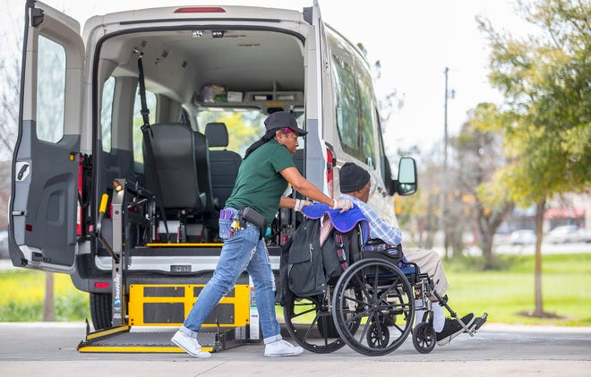 A woman escorts a man into Pflugerville Nursing and Rehab Center. The University of Texas Design Institute for Health and Austin Public Health are working on how to improve the experience of workers in long-term care centers.