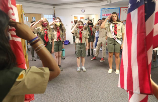 Female members of Boy Scout Troop 7270 salute the flag at the start of their meeting July 12 at the United Methodist Church in Stow.
