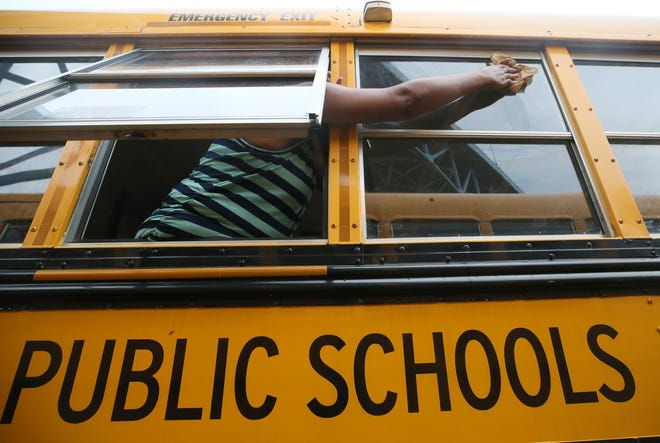A bus driver cleans the window of a bus July 13 as schools across the country prepare for the new school year.