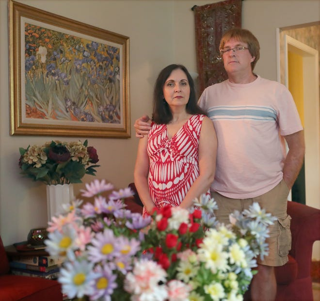 Angela Bilia and her husband, Mike Tosko, stand at their Stow home. The Stow couple were laid off from their faculty jobs last year at the University of Akron and continue to struggle to find new employment.