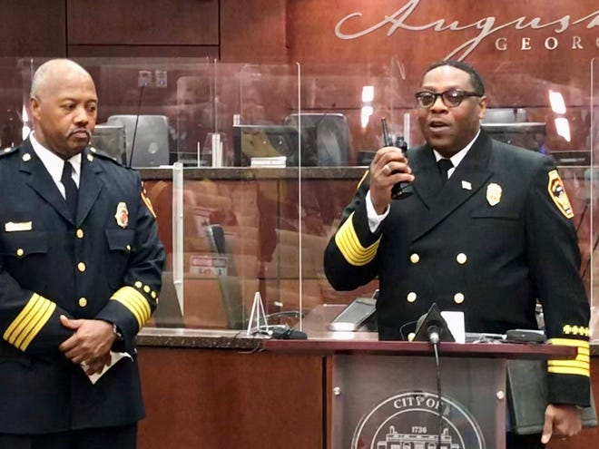 New Augusta Fire Chief Antonio Burden (right) gives a symbolic radio sign-off to interim fire chief Shaw Williams after taking the oath of office Tuesday.