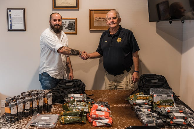 Project Tribute Foundation founder Jon Beckloff drops off over $800 worth of lifesaving first aid gear to Mike Shea, Dewey police chief, on Tuesday.