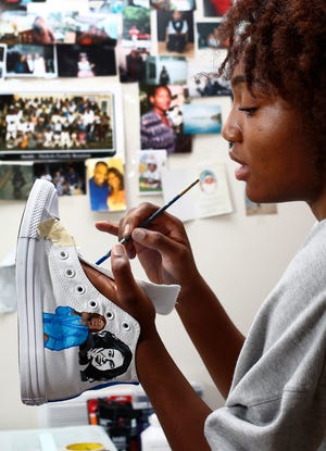 Gabrielle Anderson, 17, paints a shoe for a client with the likenesses of Michelle Obama and Kamala Harris. The Blacklick teen is a big-time basketball player who is getting attention for her artwork on sneakers.