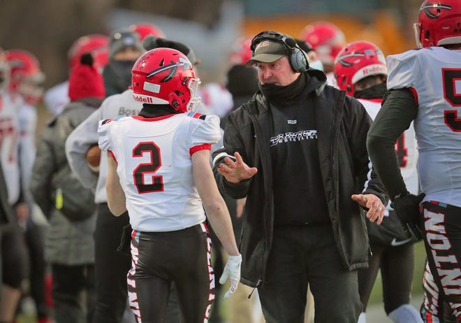 Clinton football coach Casey Randolph talks to Zak Shadley during a game in the 2021 playoffs.