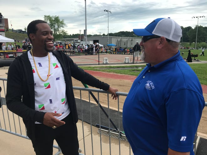 """Former Raytown South High School and Olympic sprinter Maurice Mitchell, left, visits with Grain Valley football coach David Allie at the MSHSAA State Track and Field Championships in Jefferson City. Mitchell briefly played football for Allie at Raytown South, but said he was """"too soft"""" to continue. He led Raytown South to a state title, won NCAA championships at Florida State and ran in the Olympics instead."""