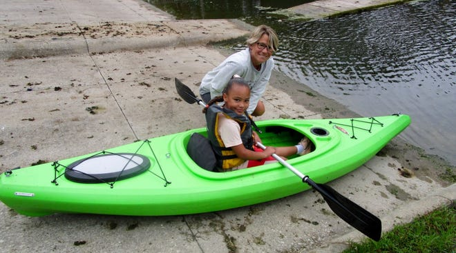 """Lola Rahn, who with her husband, Ryan Rahn, founded Foster Hope in Atkinson, helps Brielle Misfeldt into a kayak at the """"Try-A-Kayak"""" held Saturday, July 10, at Izaak Walton League, outside of Genese"""