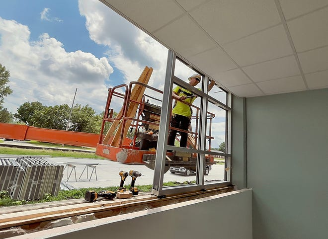 A employee of East Moline Glass installs a frame into one of the front office windows at Galesburg High School as construction continues on Tuesday.