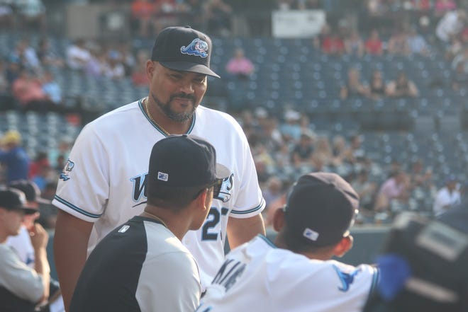 Whitecaps manager Brayan Pena talks with two of his players during a game against the Ft. Wayne TinCaps