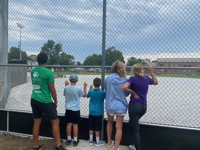 People of all ages stop to watch the current progress happening at Ralph Gale Field.