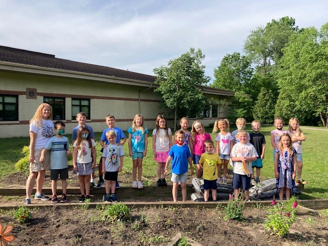 Monroe Road Elementary School teacher Jessica Snyder (left) poses with her first grade class.