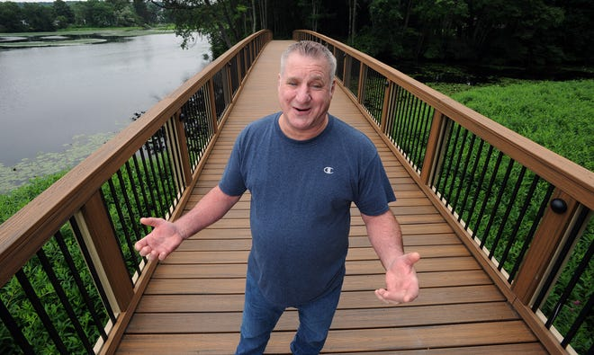 """Tom de Almeida, administrator of the """"Ashland MA. Fond Memories"""" group on Facebook, poses on the new Riverwalk Trail at Mill Pond Park, July 13, 2021."""
