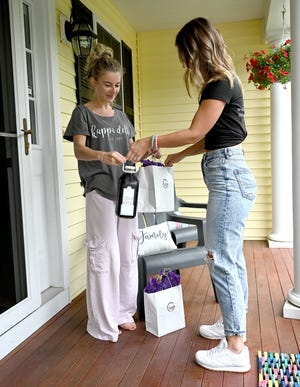 Franklin resident Nicole Mucciarone, left, accepts a delivery of Doglio Coffee cold brew from co-owner Alexa Manocchio, July 13, 2021.