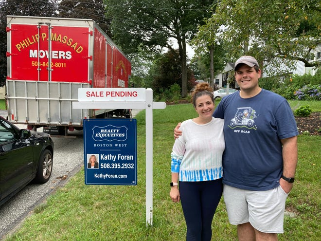 Pat and Kym Parker outside their Framingham home on Tuesday, as moving trucks packed up their belongings in preparation for the ride to their new home in Shrewsbury. The Parker's Framingham home sold for $655,000, $105,000 above the list price.