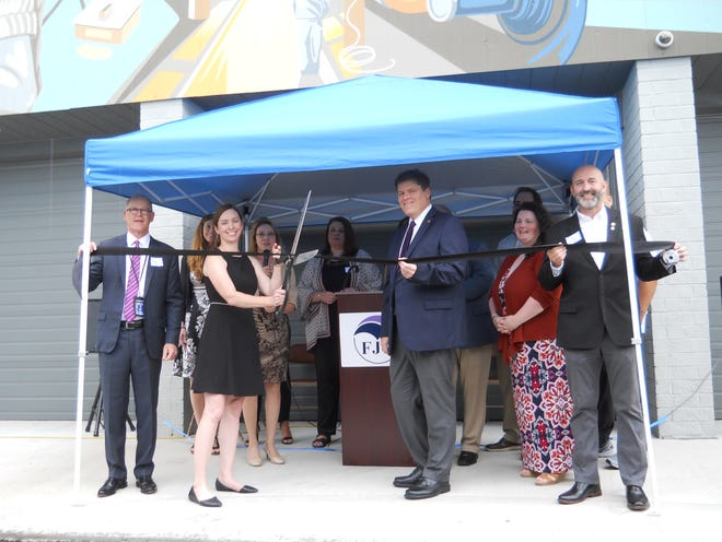 To stay out of the rain, officials gathered underneath a canopy for a ribbon cutting. Pictured (front) are ORNL Federal Credit Union CEO Colin Anderson, Anderson County Family Justice Center Executive Director Mellissa Miller and Oak Ridge City Council member Jim Dodson.