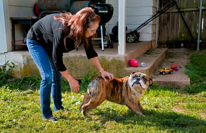 Metro Park neighborhood resident Shirley Barta plays with her dog Kush at her home. The Metro Park neighborhood association is working to resolve complaints about dogs running loose in the neighborhood, and is teaming up with a group of volunteers this month to build and mend fences for pet owners who can not afford the repairs.