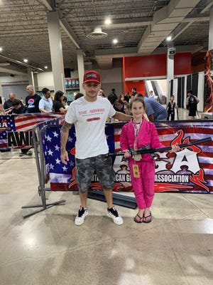 Palm Beach Gardens' Emma Bartley holds her first-place samurai sword trophy with coach Marcelo Cohen after winning the North American Grappling Association Brazilian Jiu-Jitsu Gi crown in the 60-70-pound division on June 12 at the Miami Airport Convention Center.