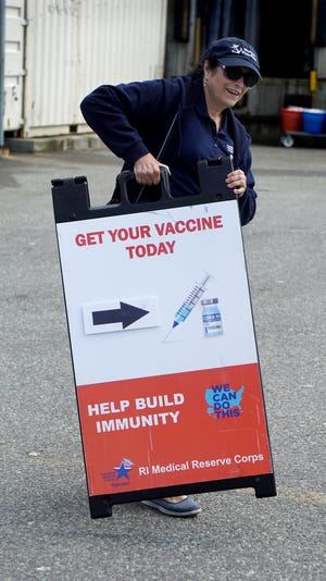 Volunteer nurse Karen O'Hara carries the vaccination sign back to the mobil testing van after an afternoon of giving COVID shots in Narragansett.