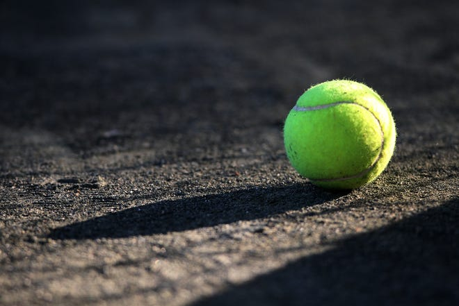 A tennis ball rests on a clay court.