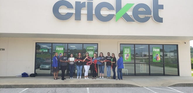 Amber Manning is holding the scissors and a certificate at the store's ribbon cutting on  July 9.