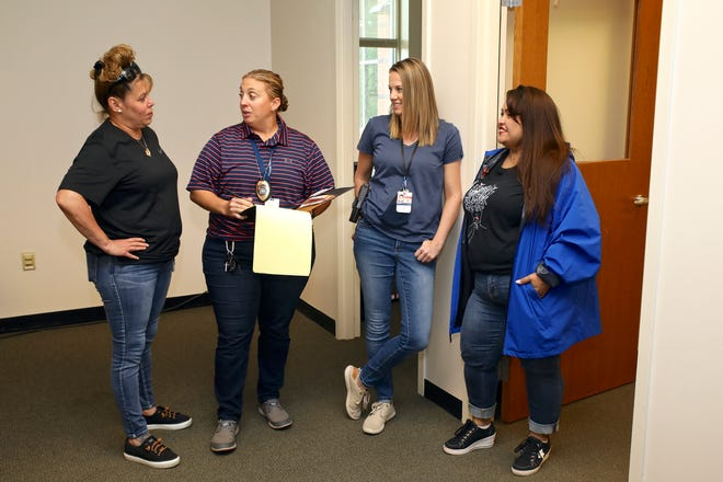 Crisis Co-Response Team members Rosecrance Mental Health Clinician Christi Wilson, left, of Poplar Grove, Detective Stacy Beaman of Rockford, Deputy Tiffany Eisman of Rockford, and Rosecrance Mental Health Clinician Victoria De La Rosa of Rockford, converse in their office Wednesday, July 7, 2021, at the Winnebago County Justice Center in Rockford. A fifth member, Detective Dave Cerasa of Rockford is not pictured.